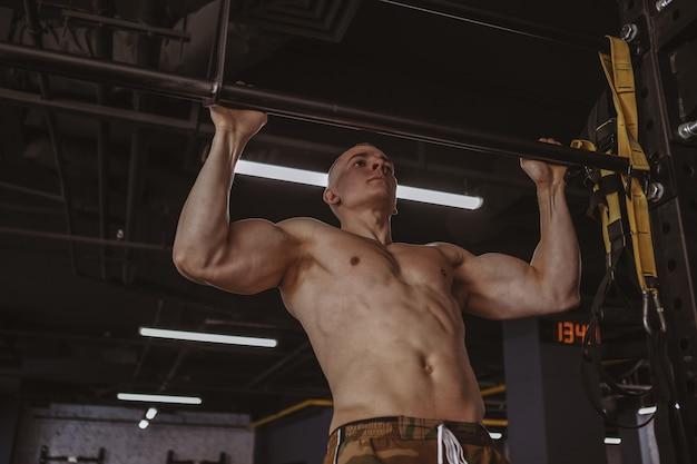 Sportowy mięśniowy mężczyzna ćwiczy przy gym