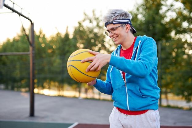 Sportowy młody chłopak w casual, lubiący koszykówkę