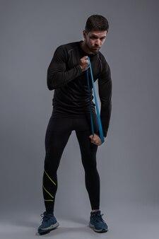 Sportowy młody człowiek ćwiczący z mini opaską oporową