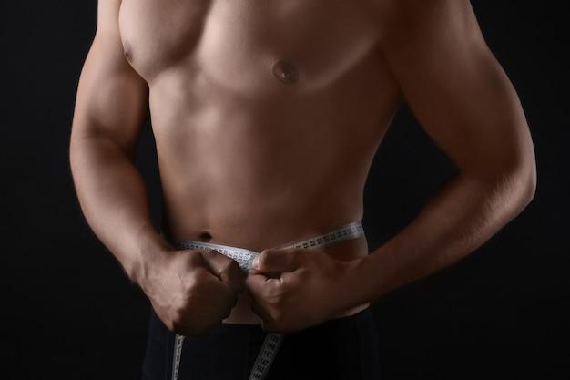 Sportowy młody człowiek mierzy jego talię