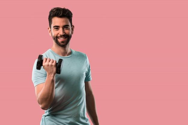 Sportowy młody człowiek robi ćwiczenie dumbbell