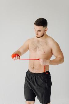 Sportowy młody człowiek robi treningi w domu, człowiek robi trening, rozgrzewa się przed ćwiczeniami wagi.