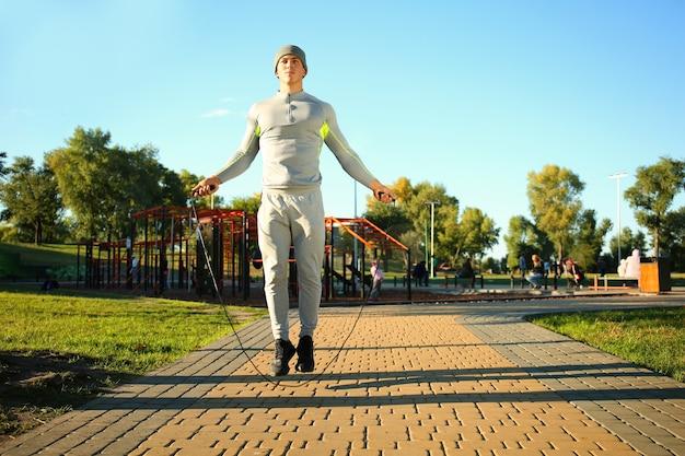 Sportowy młody człowiek skakanka w parku
