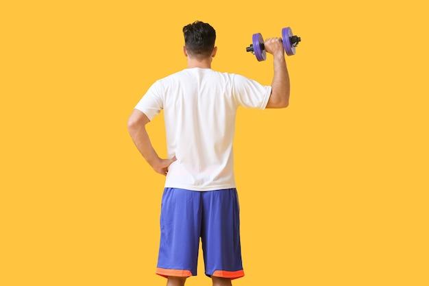 Sportowy młody człowiek trenuje z hantlami na powierzchni koloru