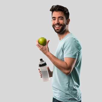 Sportowy młody człowiek trzyma jabłka i butelki