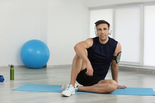 Sportowy młody człowiek w siłowni