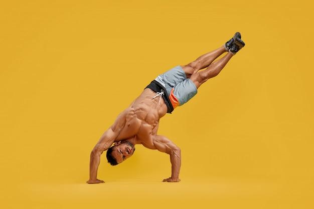 Sportowy młody człowiek wykonuje handstand wyczyn kaskaderski