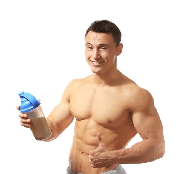 Sportowy młody człowiek z koktajlem proteinowym na białym tle