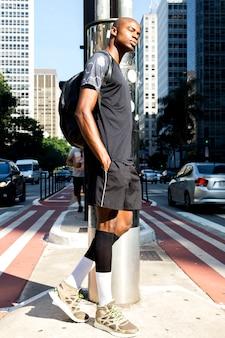 Sportowy młody człowiek z plecakiem opiera na drodze z rękami w kieszeni