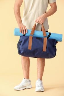 Sportowy młody człowiek z torbą i matą do jogi na beżu