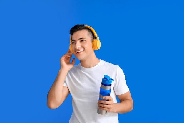 Sportowy młody człowiek ze słuchawkami i wodą w kolorze
