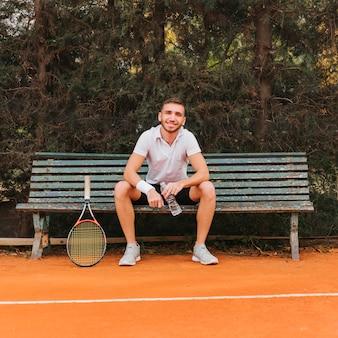 Sportowy młody gracz w tenisa obsiadanie w banku