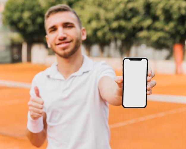 Sportowy młody gracz w tenisa pokazuje smartphone