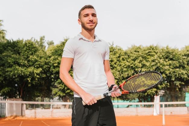 Sportowy młody gracz w tenisa pozować