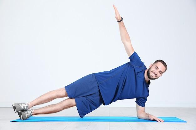 Sportowy młody mężczyzna trenujący nogi na macie w siłowni