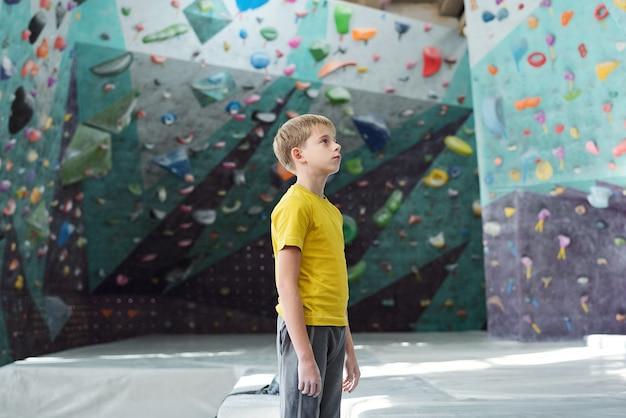 Sportowy młodzieniec w stroju sportowym, stojący pośrodku pomieszczenia do wspinaczki skałkowej i patrząc na jedną ze ścian