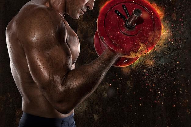 Sportowy muskularny mężczyzna biceps szkolenia na siłowni z efektem ognia