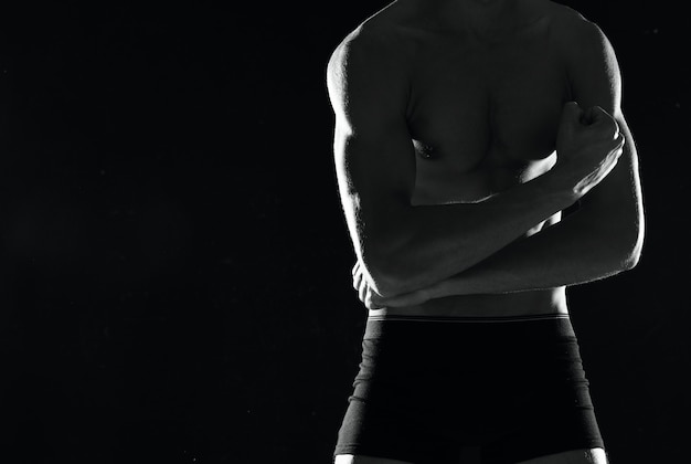 Sportowy muskularny mężczyzna w czarnych spodenkach kulturysta ciemnym tle