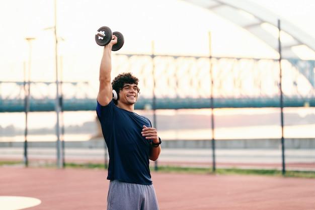 Sportowy muskularny mężczyzna z kręconymi włosami podnoszenia hantle stojąc na korcie w godzinach porannych. słuchawki na uszach.