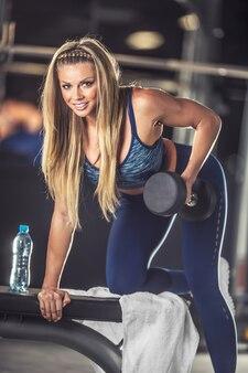 Sportowy piękna młoda kobieta ćwiczy z hantlami w siłowni.