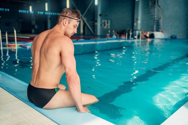 Sportowy pływak mężczyzna siedzi na krawężniku, widok z tyłu. wewnętrzny basen.