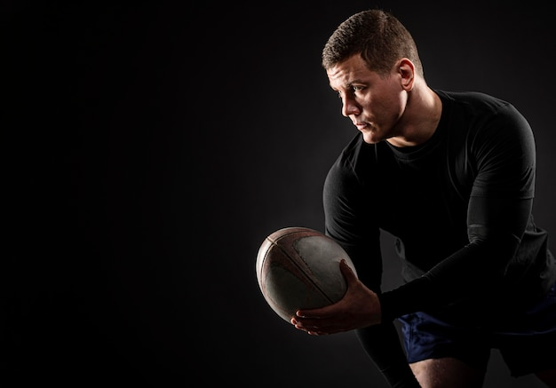 Sportowy przystojny mężczyzna rugby gracz trzyma piłkę z miejsca na kopię