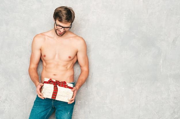 Sportowy przystojny silny mężczyzna. model zdrowego fitness lekkoatletycznego pozowanie w pobliżu szarej ściany w białej bieliźnie.