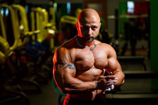 Sportowy przystojny silny mężczyzna pozowanie na tle siłowni. silny kulturysta z doskonałymi mięśniami brzucha, ramion, bicepsów, tricepsów i klatki piersiowej.