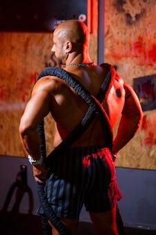 Sportowy przystojny silny mężczyzna pozowanie z liny sportowej na tle siłowni. silny kulturysta z doskonałymi mięśniami brzucha, ramion, bicepsów, tricepsów i klatki piersiowej.