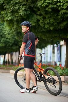 Sportowy rowerzysta w pobliżu roweru