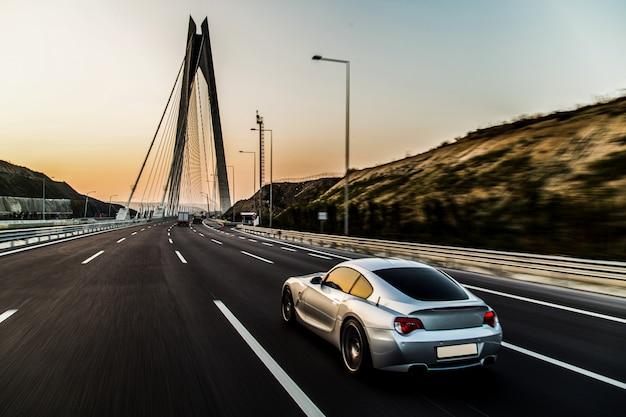 Sportowy samochód w kolorze metalicznym na moście.