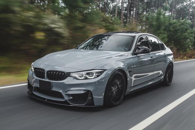 Sportowy sedan w srebrnym metalicznym kolorze na drodze.