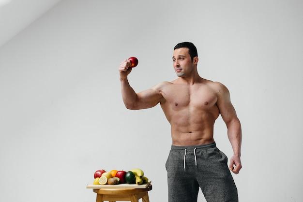 Sportowy seksowny facet pozuje na białej ścianie z jasnymi owocami. dieta. zdrowa dieta.