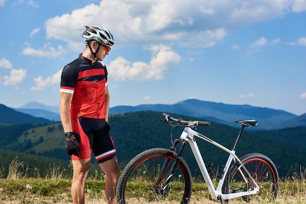 Sportowy sportowca cyklista patrzeje jego rower. góry, jasne błękitne letnie niebo w tle