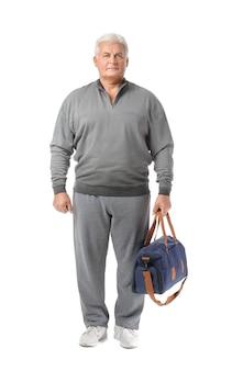 Sportowy starszy mężczyzna z torbą na białym tle