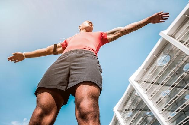Sportowy styl życia. niski kąt przystojny, sprawny mężczyzna stojący w pobliżu stadionu