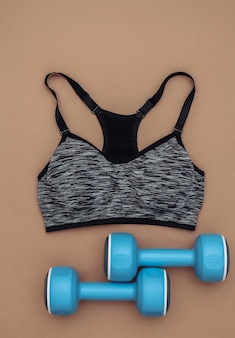 Sportowy top biustonosz, hantle na brązowym tle. sport i fitness. widok z góry. płaskie ułożenie