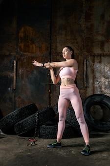 Sportowy trener kobieta robi rozciągające ramiona w starym garażu. poranna gimnastyka od kulturysty, fitness w niesamowitym miejscu