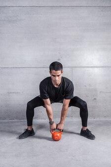 Sportowy trener pokazujący ćwiczenia z kettlebell