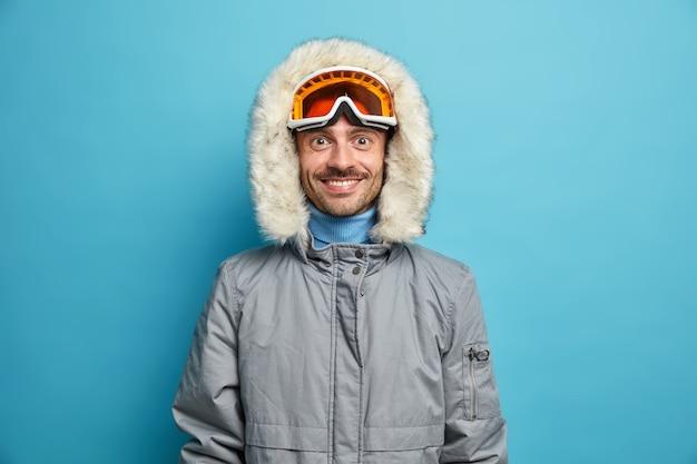 Sportowy, zadowolony człowiek lubi sporty zimowe rekreacji, uśmiechy z radością nosi gogle narciarskie i szarą kurtkę.