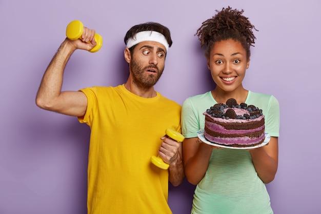 Sportowy, zdrowy styl życia przeciwko fast foodom. zdziwiony sportowiec trzyma hantle