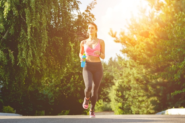 Sportsmenka biegająca z butelką na słonecznym tle