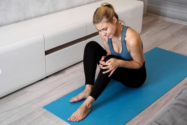 Sportsmenka cierpiąca na ból kolana siedzi na podłodze na macie do jogi w salonie