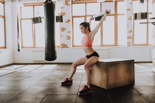 Sportsmenka jest rozciąganie z ręcznikiem w siłowni