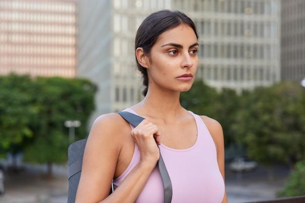 Sportsmenka nosi gumową matę fitness do ćwiczeń jogi, regularnie patrzy poważnie na ćwiczenia z kamerą, aby zachować zdrowie, ubrana w odzież sportową, na rozmytych pozycjach