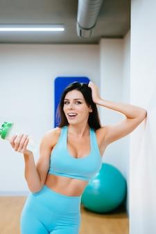 Sportsmenka odpoczywa wodę pitną na schodkach w gym i