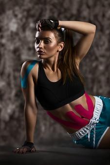 Sportsmenka odpoczywa z naklejkami na brzuchu i ramionach
