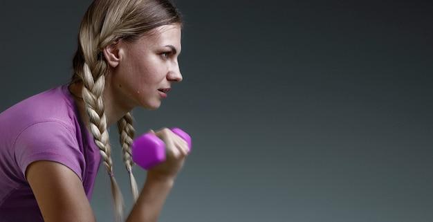 Sportsmenka poci się na siłowni z fioletowymi hantlami