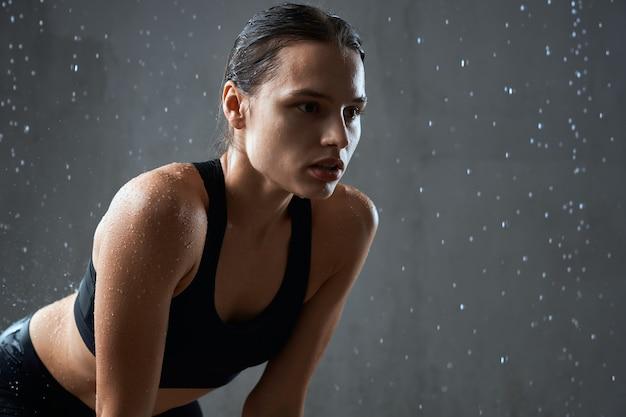 Sportsmenka pozuje w sportowej odzieży odizolowanej na szaro