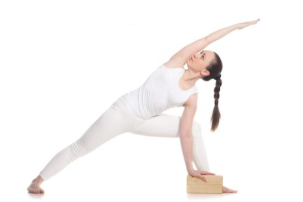 Sportsmenka robi ćwiczenia jogi z drewnianym bloku